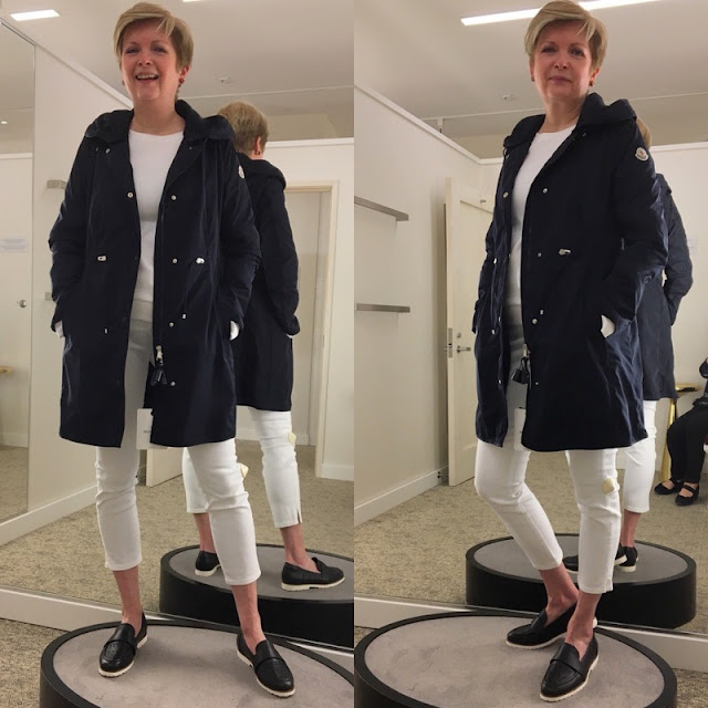 woman in white jeans and tee and a navy coat