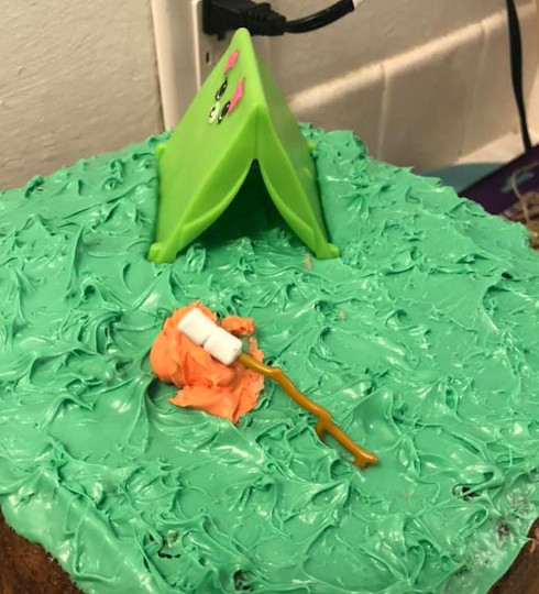 This shows the top of the cake with green frosting , a toy tent, and campfire scene.