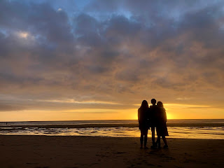 Family standing at sunset, Watergate Bay