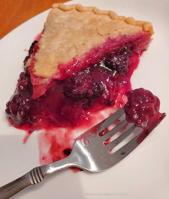 this is a berry pie made from scratch on a white plate