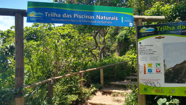 A big blue and green sign with the name Trilha das Piscinas Naturais written on it.