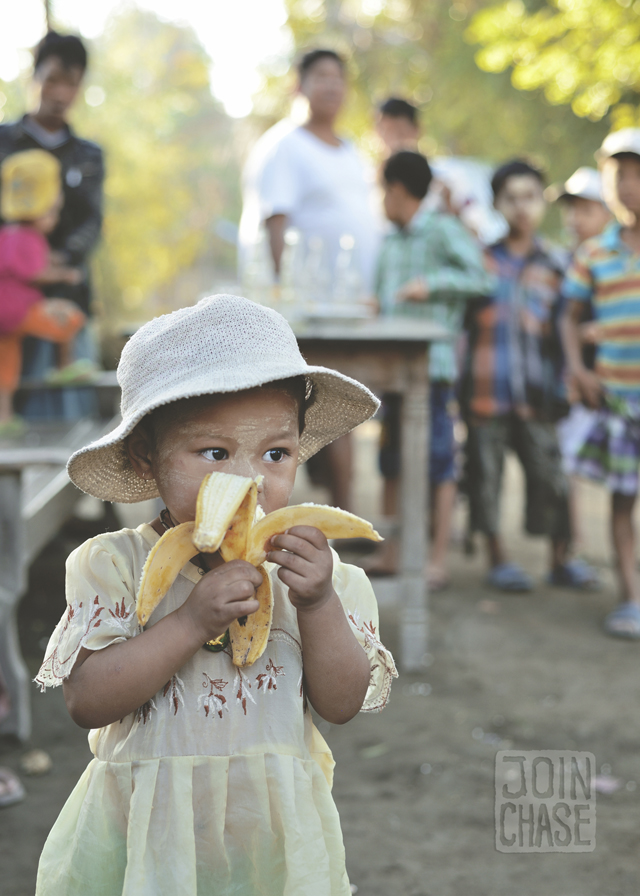 A little girl eats a banana during the filming the last scene for the Coca-Cola Myanmar commercial, Sagaing Division.