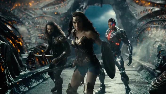 Imagem: cena do filme na qual Aquaman, Mulher-Maravilha e Ciborgue entram dentro do covil alienígena e estão em posição de ataque, ao redor tudo parece metálico e distorcido, como se fosse uma nave alienígena e energia amarela e chamejante atravessa as paredes ao redor.