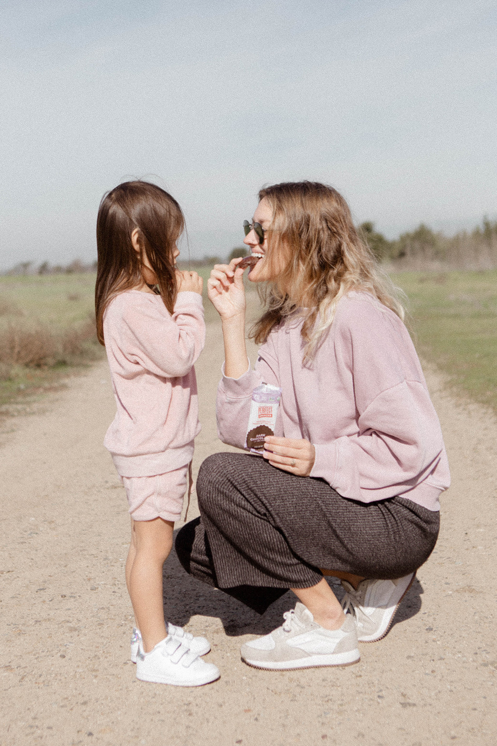 mother and daugther in matching sporty outfits eat healthy snacks