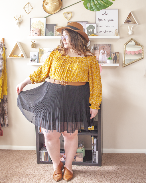 An outfit consisting of a brown panama hat, a yellow microfloral long sleeve off the shoulder blouse tucked into a black pleated mini skirt and brown d'orsay flats.