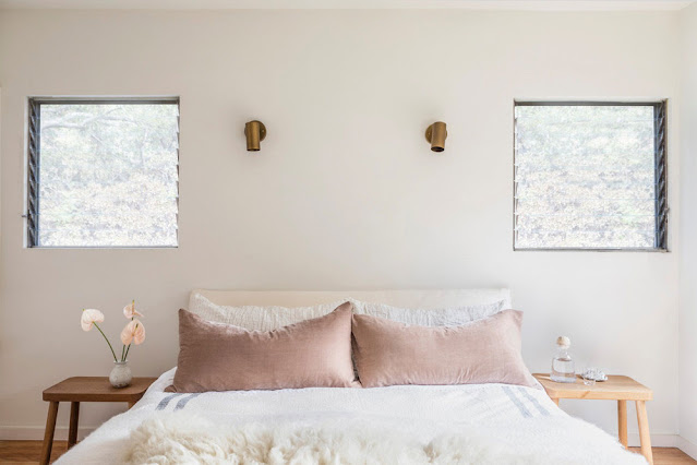 neutral bedroom with blush velvet pillows and gold wall sconces