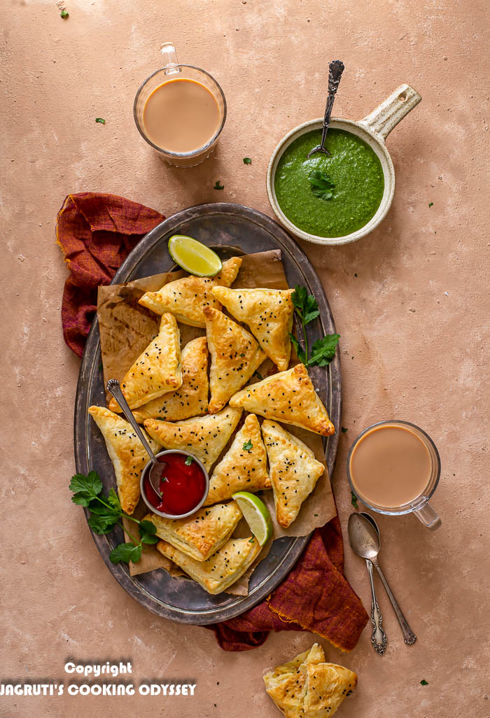 Air fried punjabi samosa puffs made using ready rolled puff pastry are served in a metal tray along with ketchup, green chutney and masala chai on a beige backdrop.