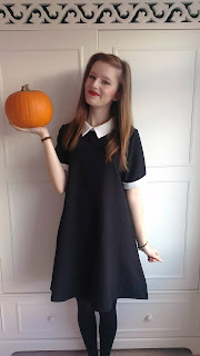 Me wearing my Wednesday Adam's style dress, a picture for my first ever lookbook, holding pumpkin in right hand and smiling merrily to the camera with red lips.