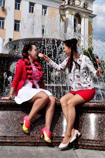 Две девушки на фонтане кушают пончик