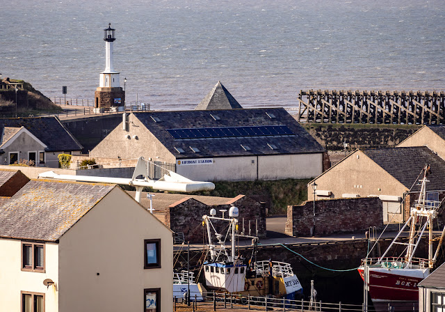 Photo of view across the rooftops to Maryport Lighthouse and the Solway Firth