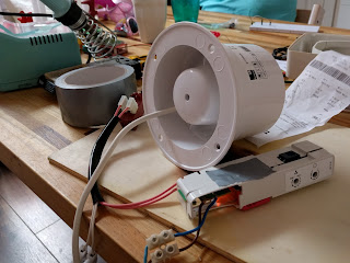 It works! Note the piece of paper lifted by the air flow, the new orange capacitor peeking through, and the flange still being attached to the new fan.