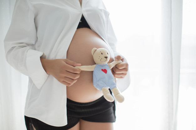 Mãe segurando um ursinho na frente da barriga