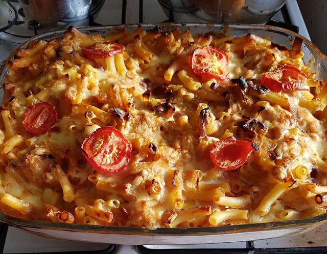 A large roasting dish with cooked leek macaroni cheese browned on top and melted cheese