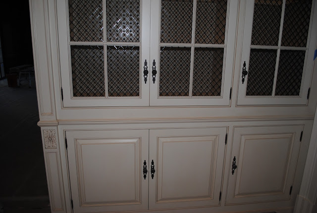 Detail of white glazed French Country kitchen glass front cabinetry in Enchanted Home Tina's kitchen