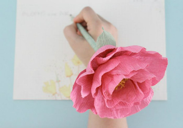 hand holding ink pen with realistic pink crepe paper peony attached to top