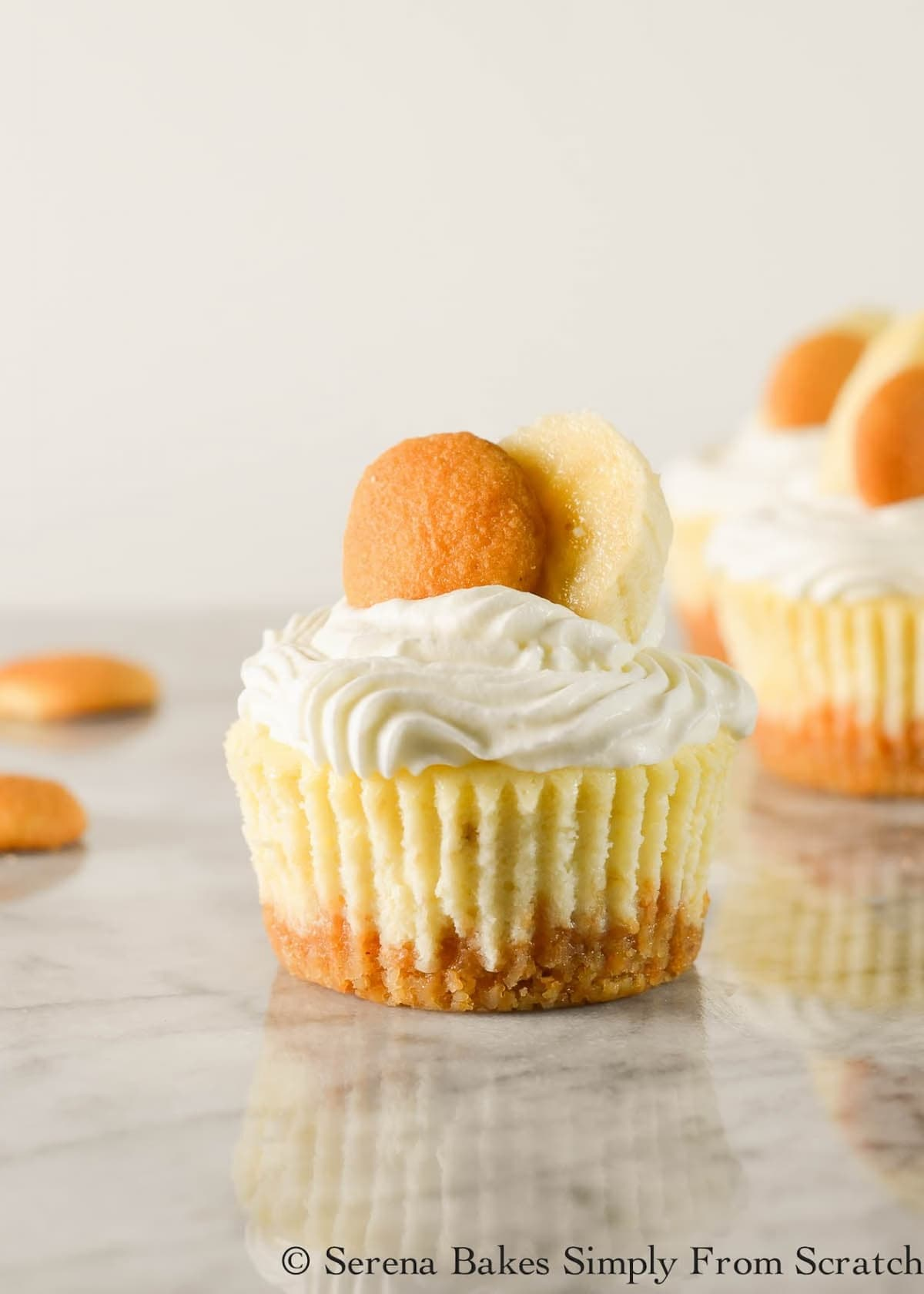 A Mini Banana Pudding Cheesecake topped with whipped cream, a mini nilla wafer, and slice of banana with 2 additional nilla wafers on white marble with additional Mini Banana Pudding Cheesecakes in the background.