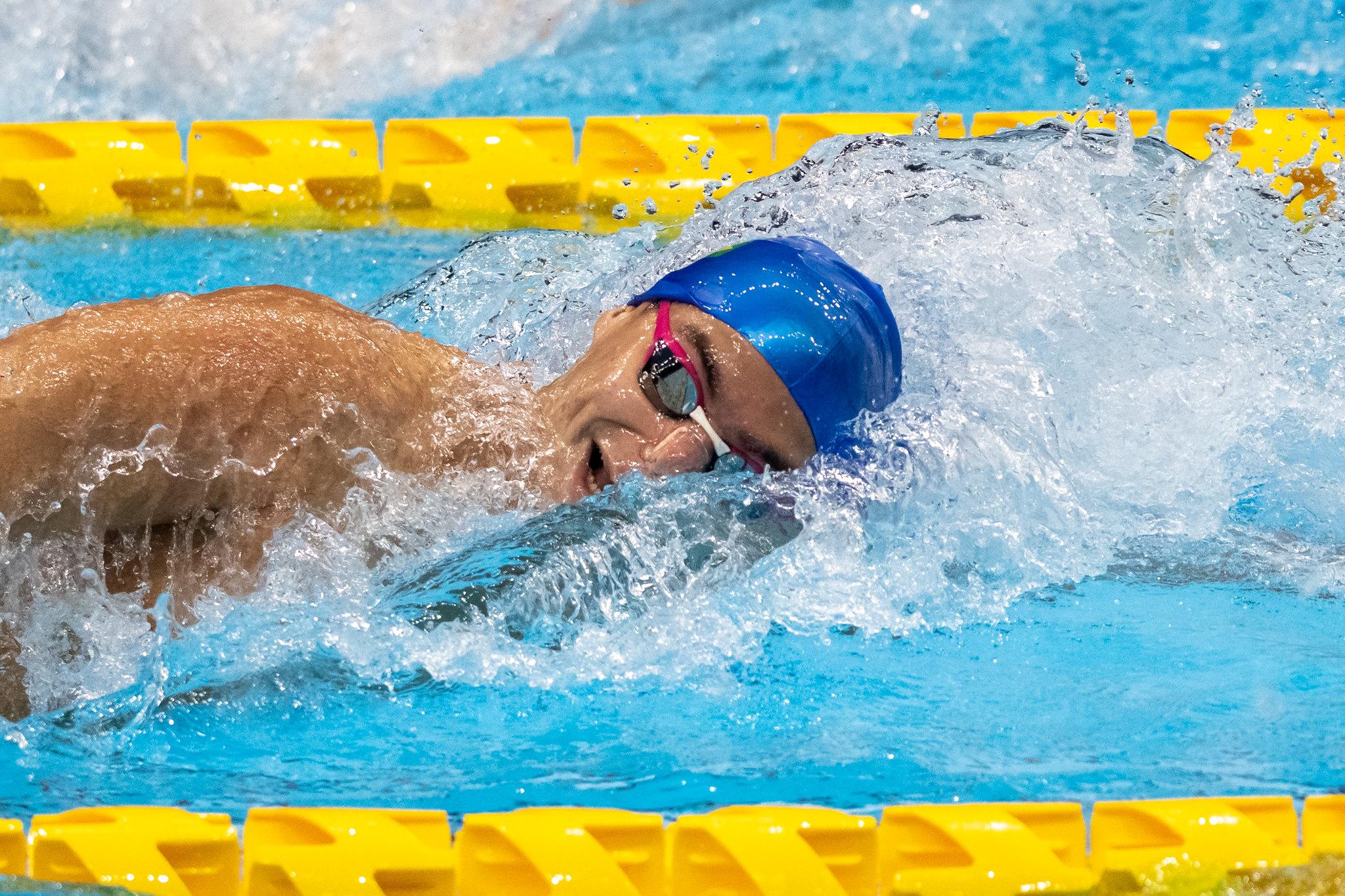 Gabriel Bandeira nada de touca azul e óculos pretos com detalhe rosa