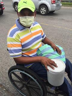 A Honduran man on the street begging holding a food bag