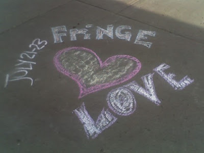 A chalk sidewalk drawing promoting Athabasca's Fringe Festival.  A pink heart with the words Fringe Love