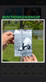 в руках фотография которая напоминает детство около дерева