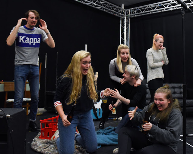 Photo of a group of young people in a rehearsal room, they all look excited.
