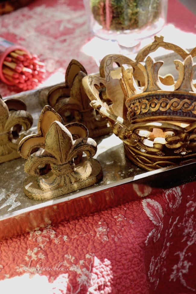 Metal fleur de lis card holders mingle with gold crowns in the French Country Christmas greenhouse