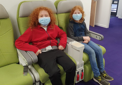 waiting room full of flight seats from aeroplane with my 2 boys sitting politely, wearing COVID masks