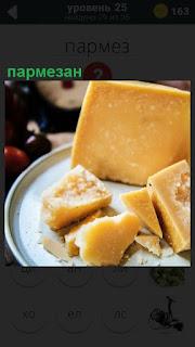 На тарелке лежит сыр пармезан крупным куском и порезаны ломтики