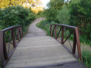 a short bridge with ruddy metal rails crosses Bacon Creek along the trails at Bacon Creek Park