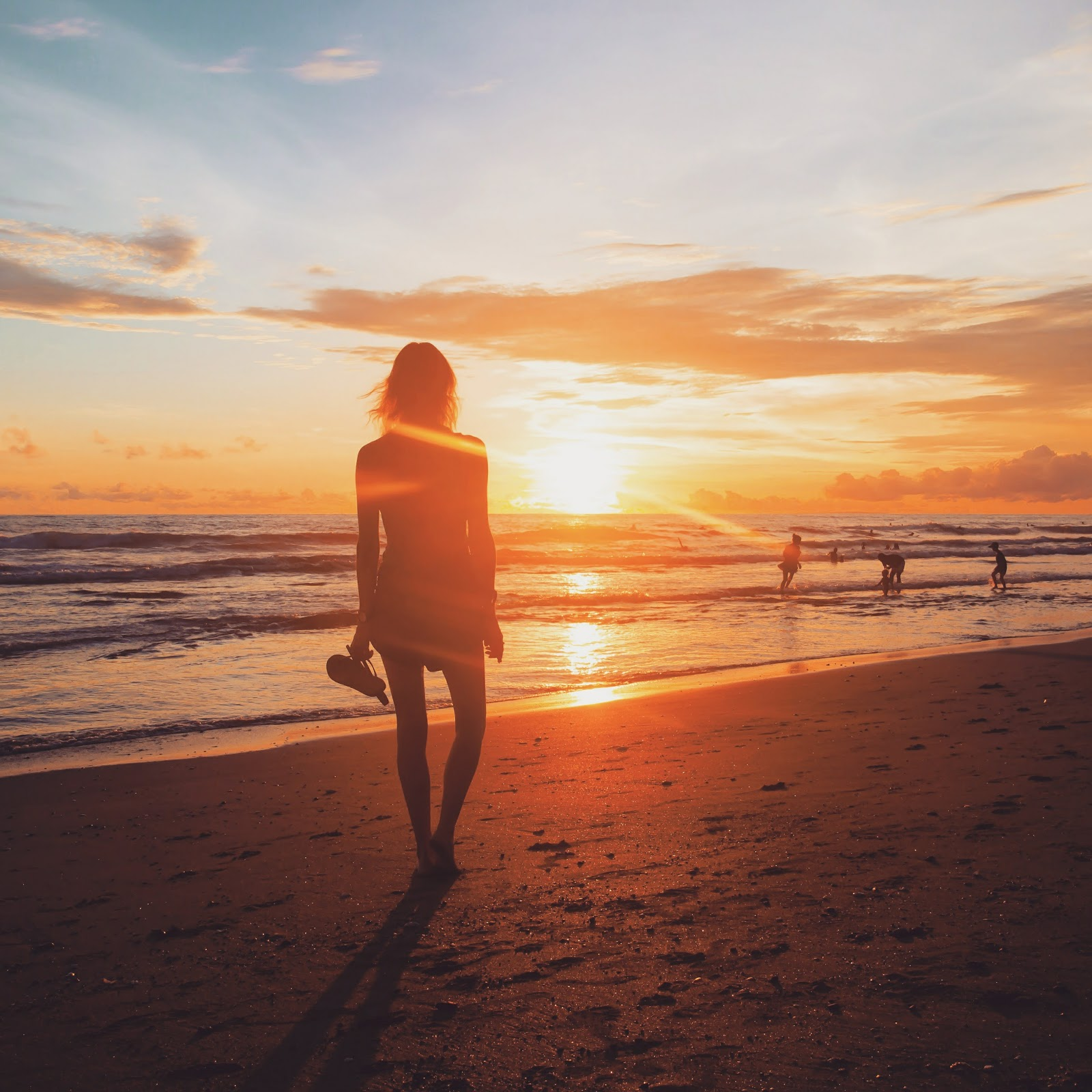 Fashion and travel blogger, Alison Hutchinson, walking along the beach at sunset in Canggu, Bali, Indonesia