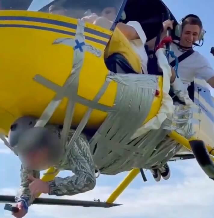 homem voa fora do helicoptero