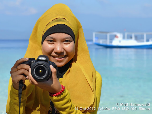 street portrait, Indonesia, Central Sulawesi, young Indonesian Muslim lady, photographer, yellow hijab, beach, Nikon DSLR D3200, charming, outgoing, smiling
