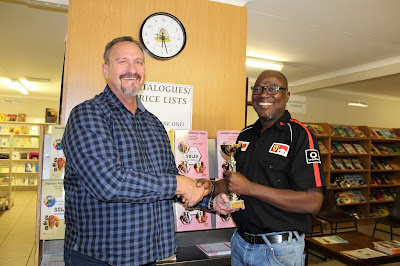 Deon de Waal of NPH handing a trophy to  John Muyambango of PPS,  who accepted it on behalf of the school