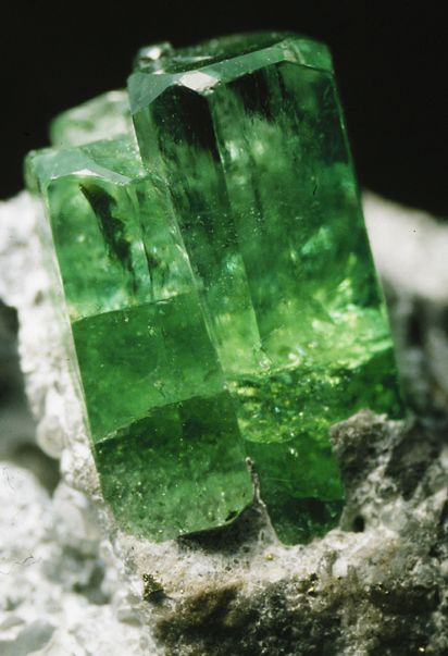 An emerald crystal displayed on a rock.