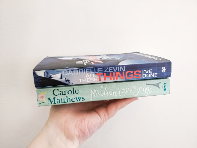 A fair skinned hand holing up a stack of two books against a white background. The Bottom book is a pale blue/ green colour with a drawn pink flower on the left side followed by Carole Matthews in darker green writing, followed by Million Love Songs in script writing in white. There is a small angled Eiffel tower drawing on the right end. The Top book is blue and balck toned with a woman's face looking down with black hair covering the side of her face and subtle make up on, in the left corner The text down the spine reads Gabrielle Zevin with All These Things I've done below in white and red writing.