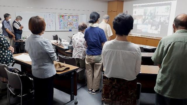 垂水区の試聴会で黙禱をささげる参加者(9日)