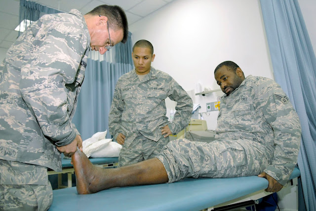 A physician examines a man's foot