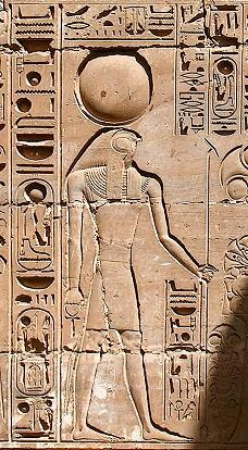 Khonsu, wearing the lunar crescent with the moon disc, and holding the ankh and uas scepter. Wall relief from Karnak.