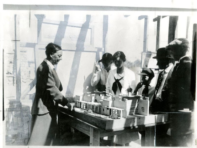 Alice Constance Austin showing model of house to Llano del Rio colonists, May 1, 1917. (Yale Collection of Western Americana, Beinecke Rare Book and Manuscript Library)