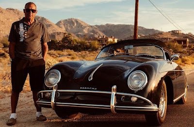 Chad McQueen posing for a photo with his car