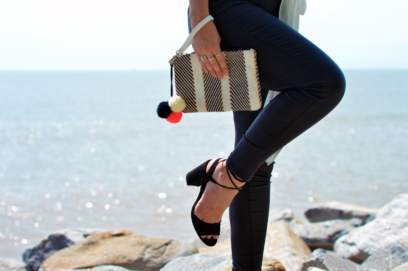 close up photo of lace up black heels pom pom clutch leather pants