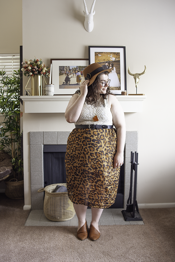 An outfit consisting of a brown panama hat, a sleeveless white lack dress worn as a top, a leopard print scarf worn as a skirt and brown d'orsay flats.