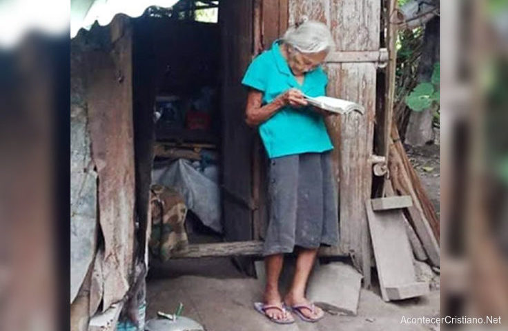 Anciana leyendo Biblia en cabaña