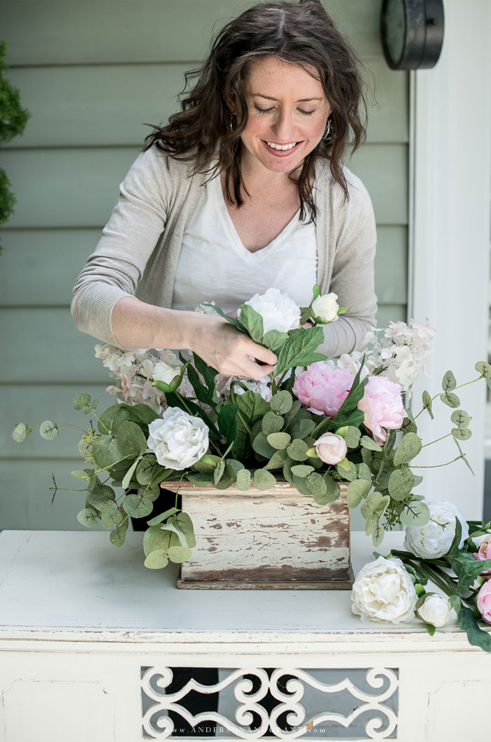 Adding pink and white peonies to flower arrangment