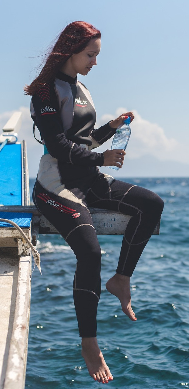 Woman diver drinking water.