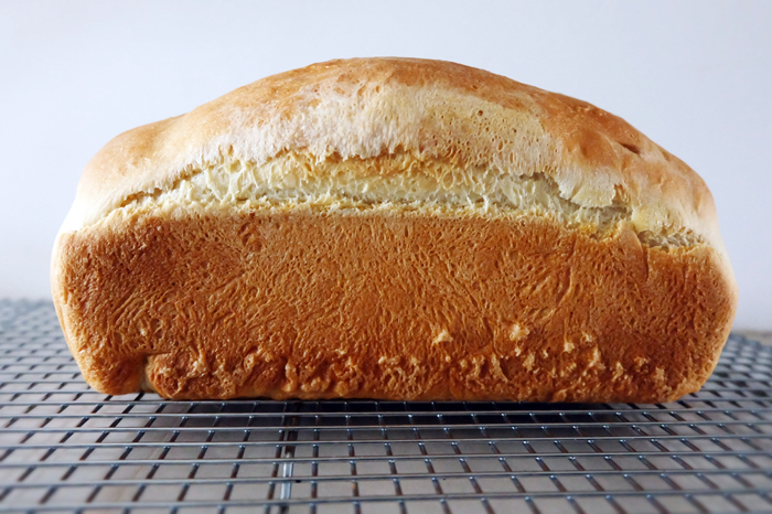 side view of baked buttermilk bread loaf on rack