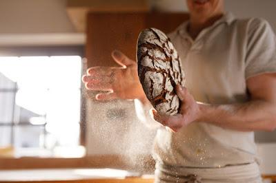 Manlig bagare med brödkaka i händerna vid mjöligt bakbord.