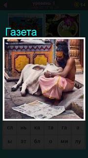 мужчина с коровой сидит и на земле лежит газета в игре 667 слов 1 уровень