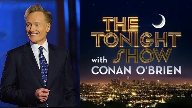 Photo of Conan O'Brien, a fair-skinned man with reddish-blond hair seen from the waist up smiling in a navy blazer, white shirt, and patterned blue tie, next to the 'Tonight Show with Conan O'Brien' title card, depicting a crescent moon in the night sky over a glowing Los Angeles cityscape