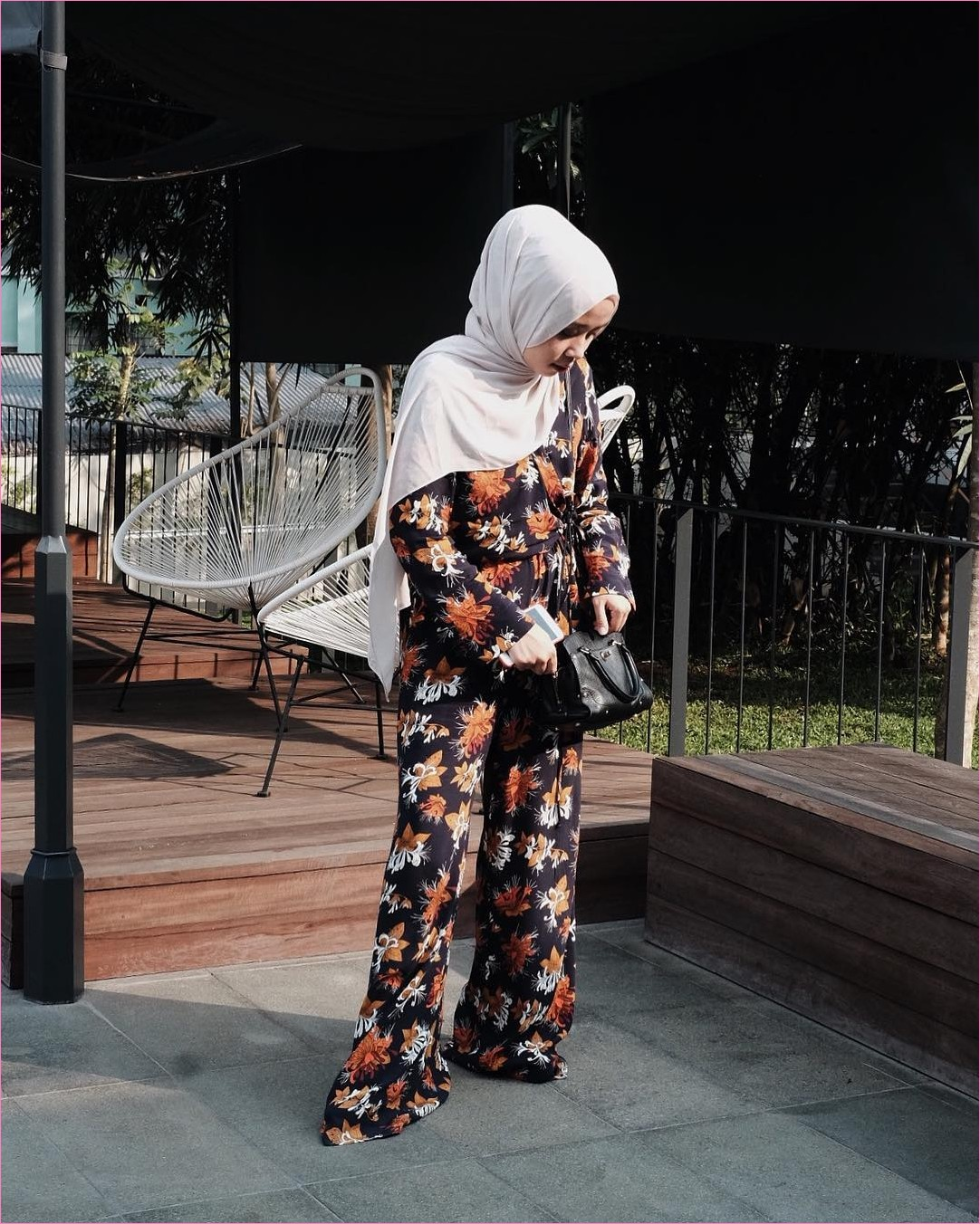 Outfit Baju Hijab Casual Untuk Ke Kantor Ala Selebgam 2018 sling bags hitam jumpsuit bermotif daun hitam oren pashmina polos putih krem muda ciput rajut handphone high heels wedges gaya casual kain katun rayon sutra ootd outfit ootd 2018 selebgram kursi kayu pohon hijau pager abu tua